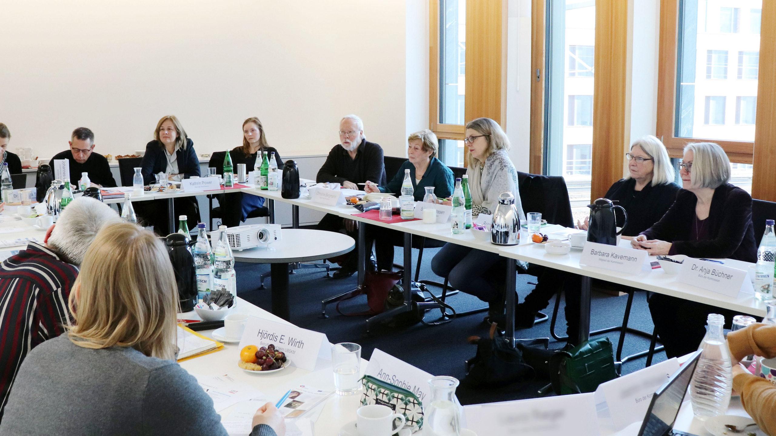 Mehrere Frauen und Männer sitzen an einem langen Tisch und sprechen miteinander oder hören zu.