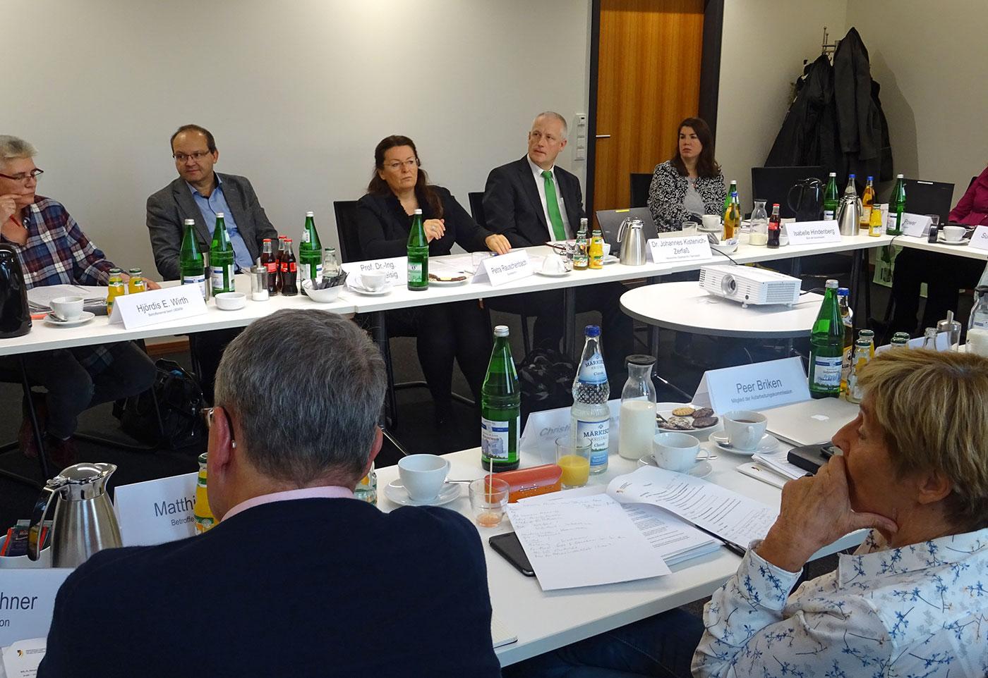 Mehrere Personen sitzen um einen Tisch und diskutieren.