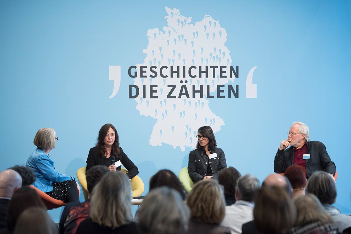 Vier Menschen sitzen auf einer Bühne. Das Publikum hört zu.