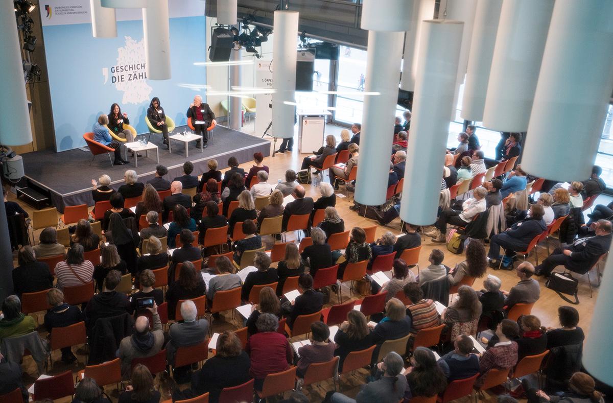 Blick in einen Saal mit vielen Menschen als Publikum. Vorne die Bühne