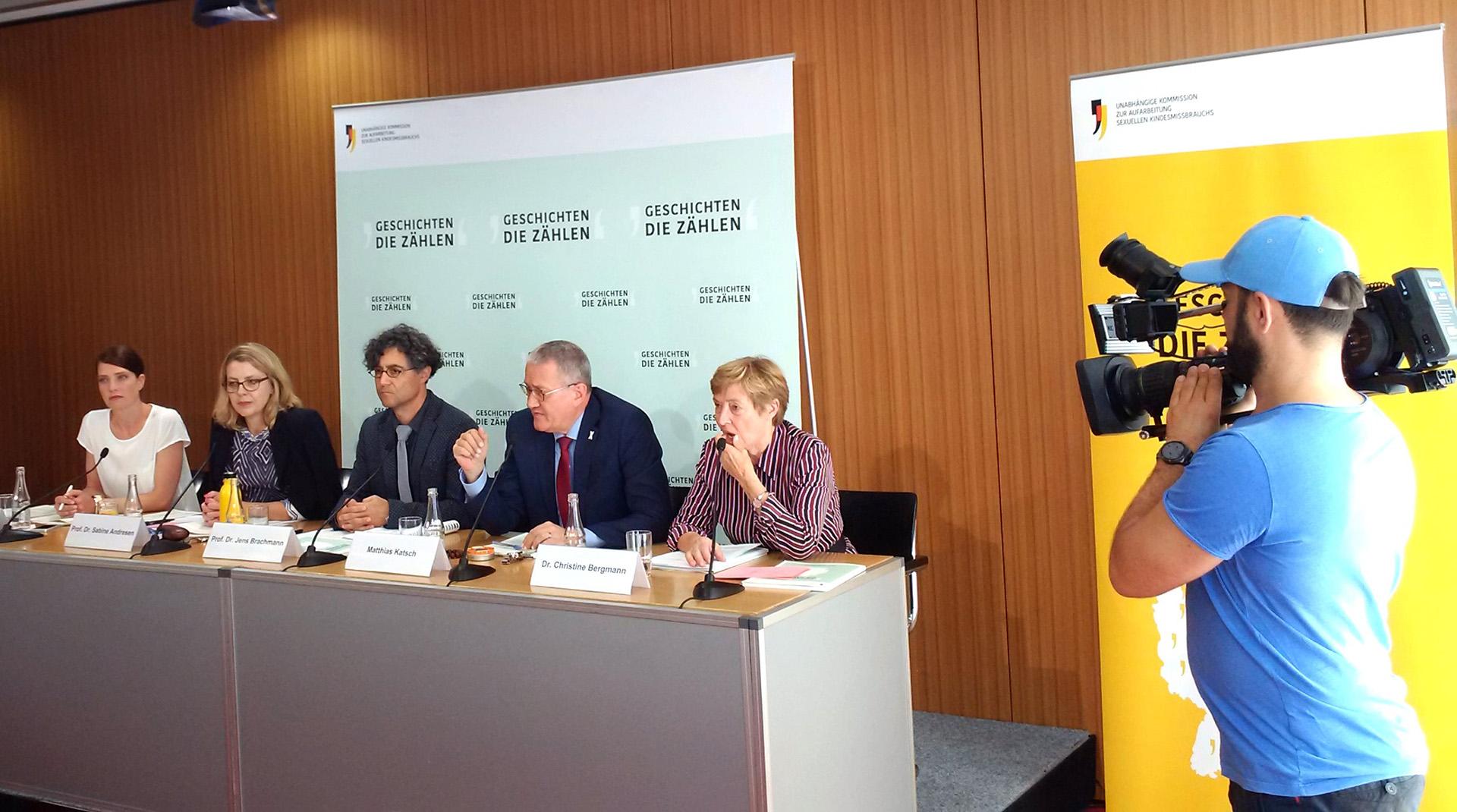 Fünf Personen sitzen hinter einem Pult auf einer Bühne und werden von einem Mann gefilmt. Es handelt sich um eine Pressekonferenz.
