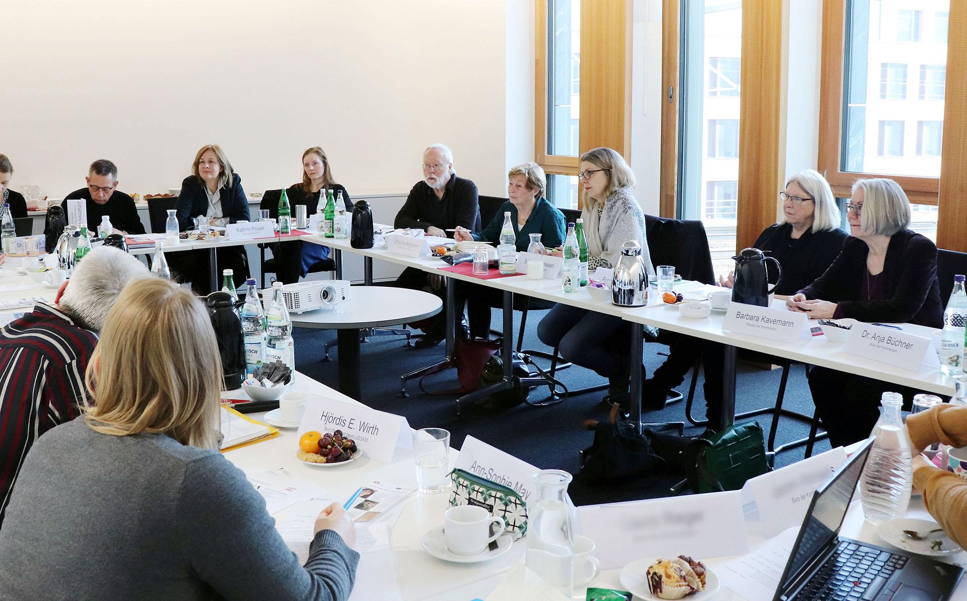 Frauen und Männer sitzen an einem Tisch in einem Raum.