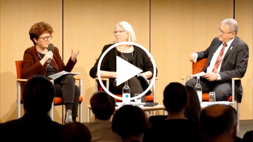 Eine Frau spricht in ein Mikrofon. Neben ihr auf der Bühne sitzen seine Frau und ein Mann.