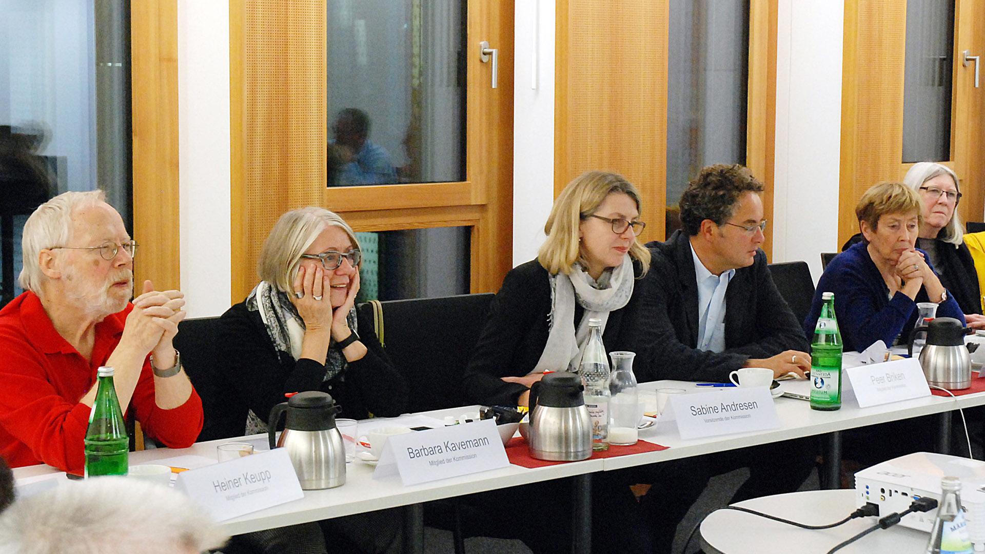 Die sechs Kommissionsmitglieder sitzen in einer Reihe an Tischen.