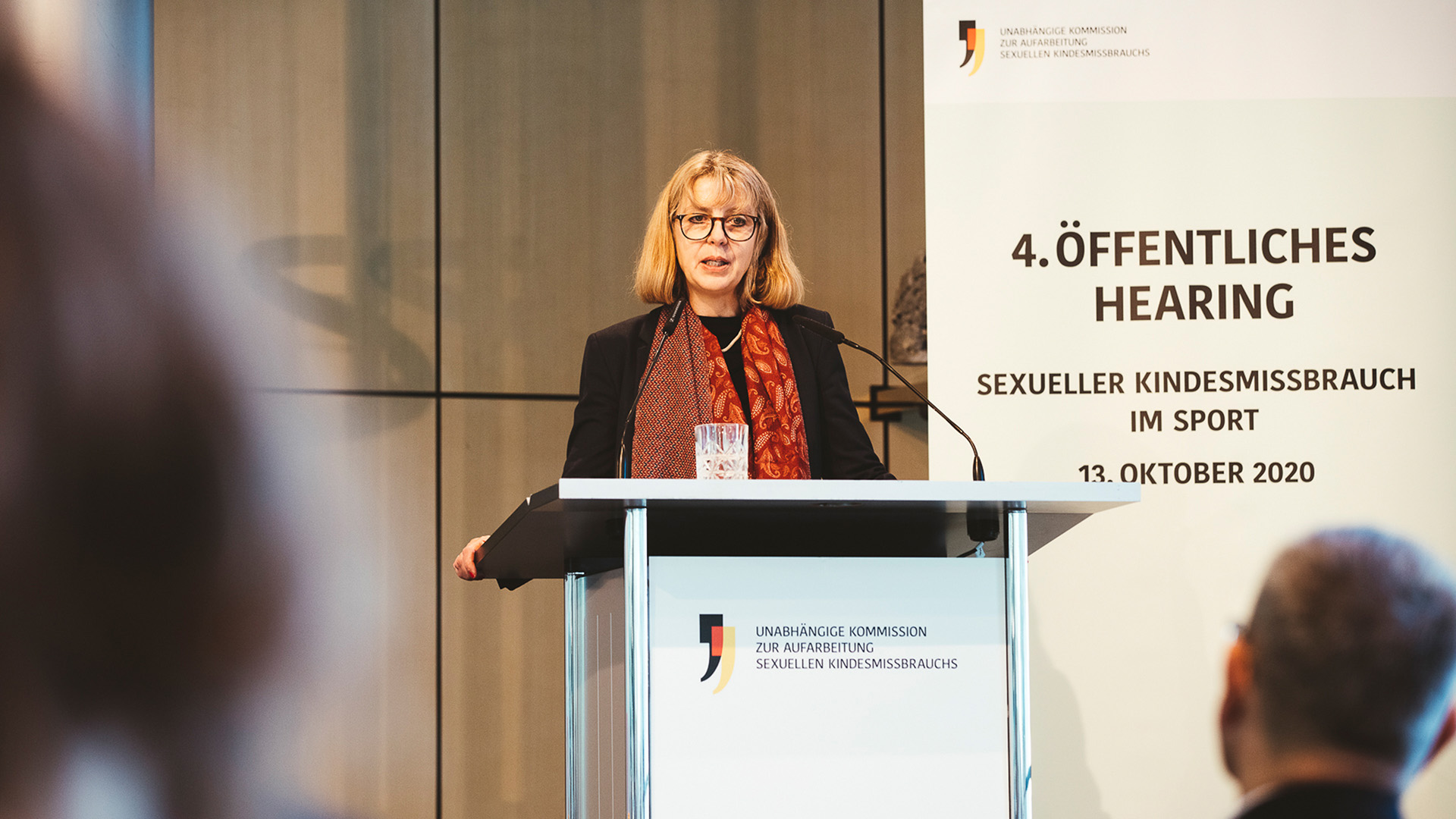 Eine Frau steht an einem Redepult und spricht. Die Frau ist Sabine Andresen.