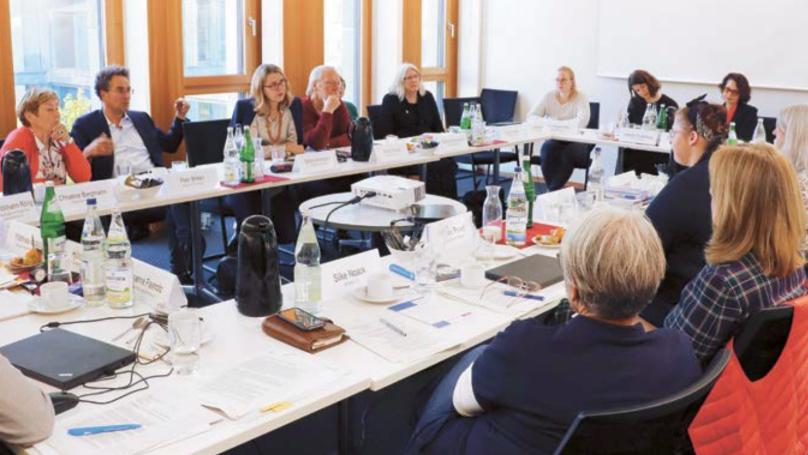 Eine Gruppe von Menschen sitzt um einen Tisch herum und spricht miteinander. Unter ihnen befinden sich auch Mitglieder der Kommission.