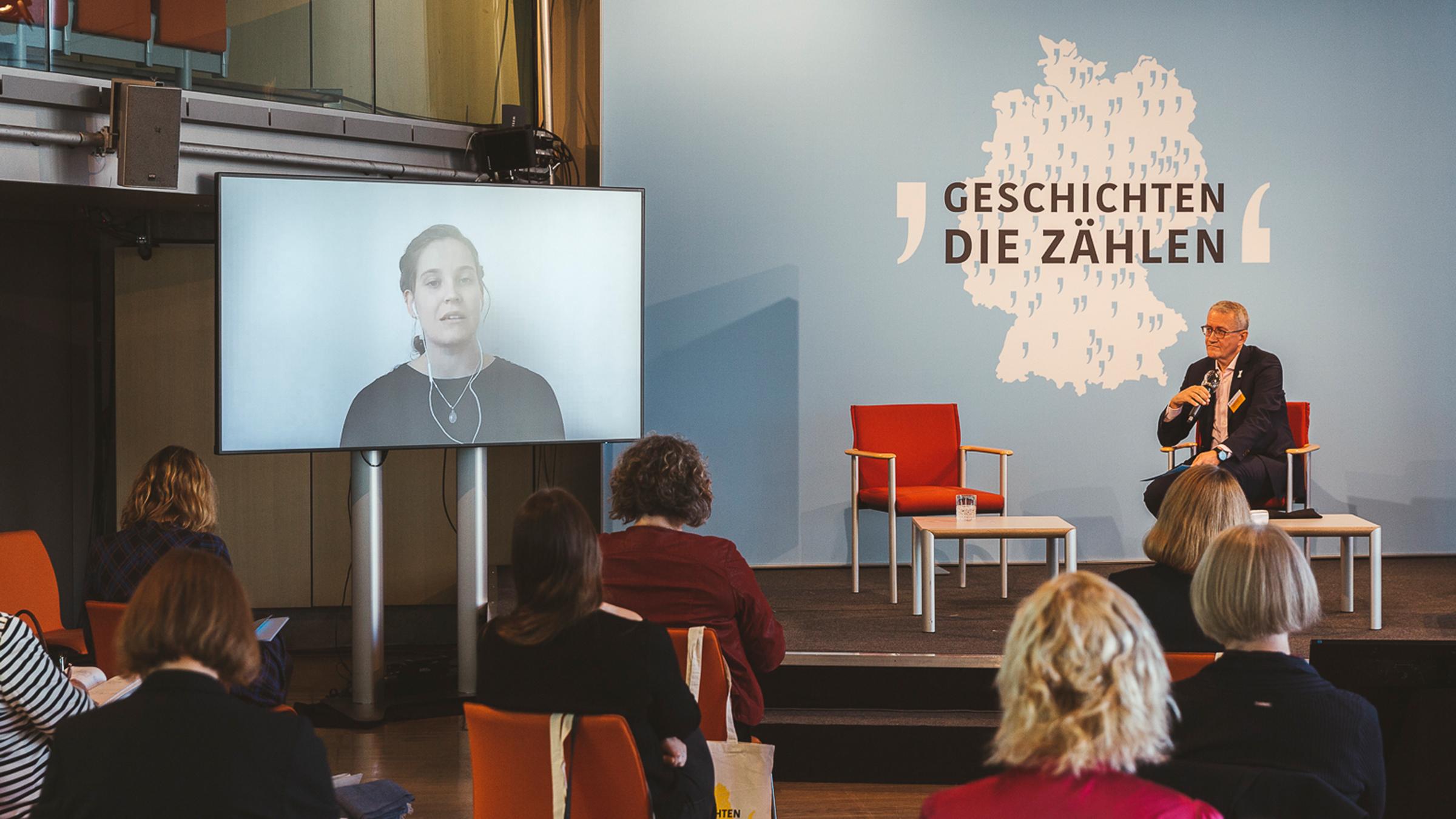 Ein Mann sitzt auf einem Podium und spricht mit einer Frau, auf einem Bildschirm.