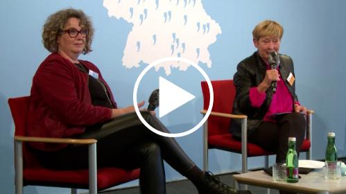 Zwei Frauen sitzen auf einer Bühne. Eine der Frauen spricht in ein Mikrofon