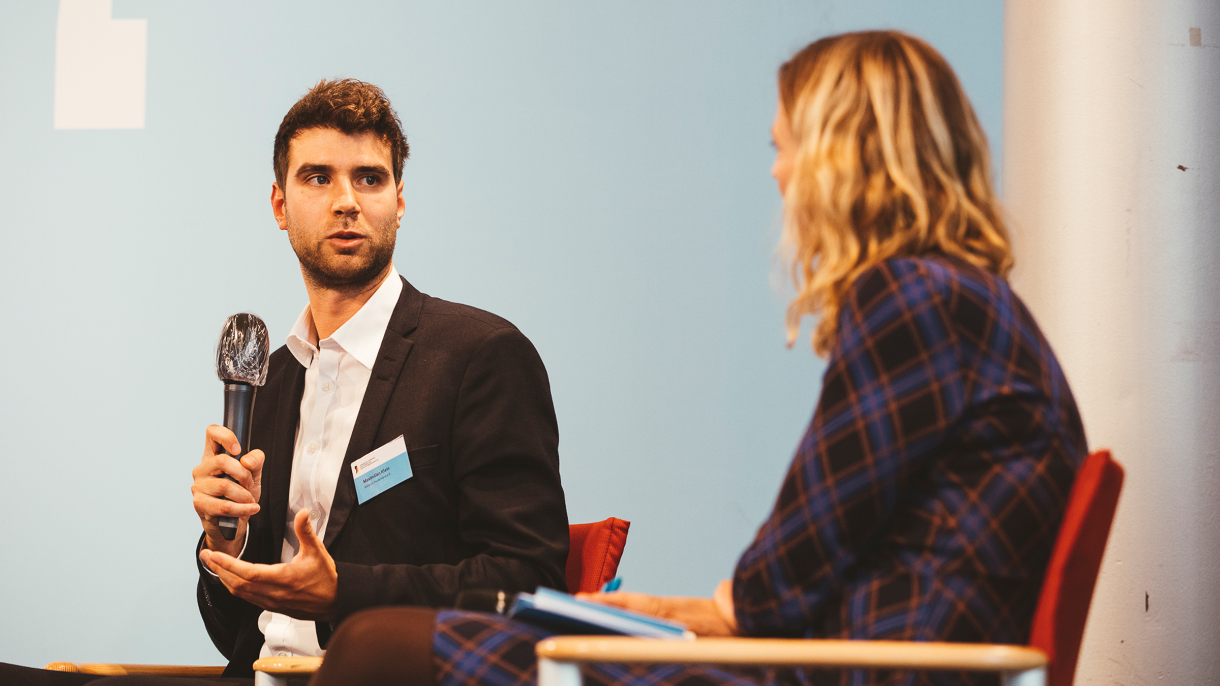 Ein Mann und eine Frau sitzen sich gegenüber. Der Mann spricht mit der Frau.