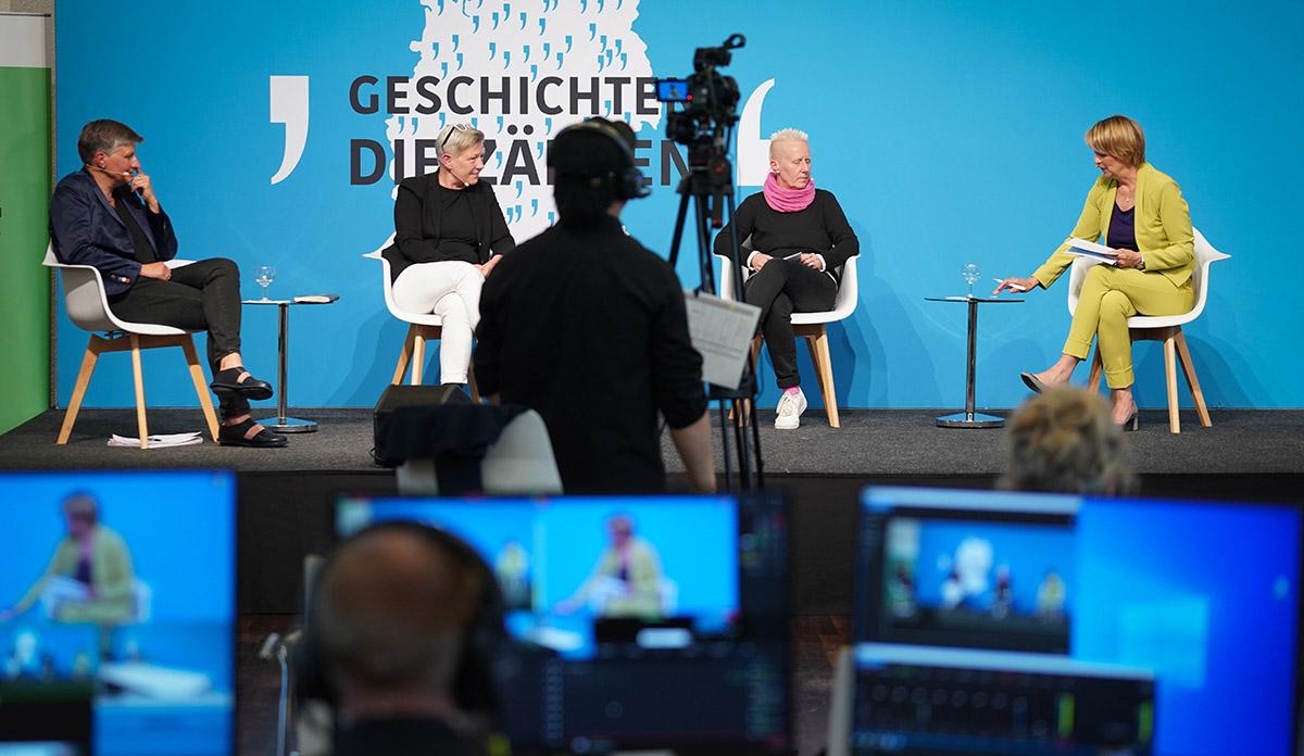 Vier Frauen sitzen auf einer Bühne und sprechen miteinander. Vor der Bühne befinden sich eine Kamera und Bildschirme.