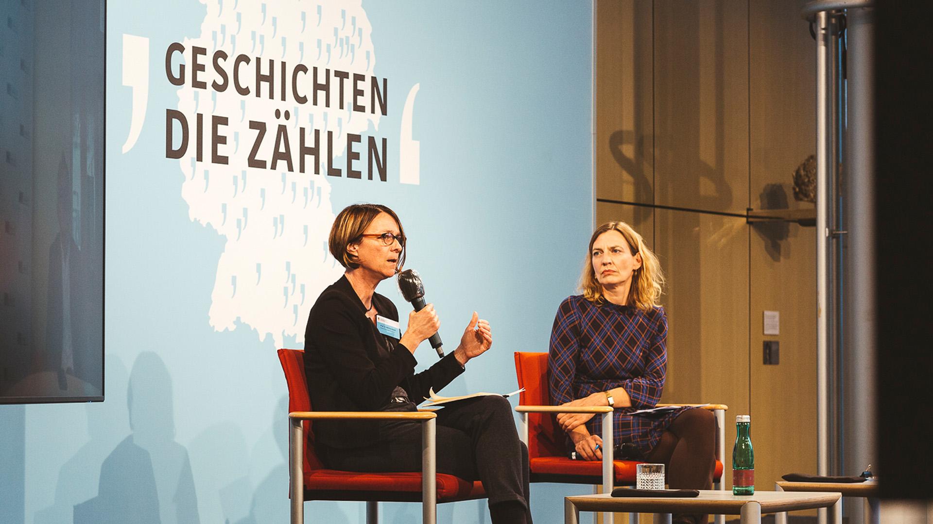 Zwei Frauen sitzen auf eine Bühne. Die eine Frau spricht in eine Mikrofon.
