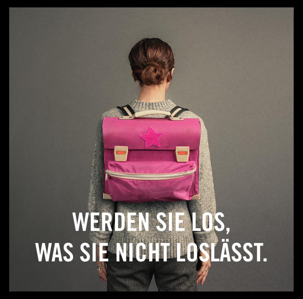 Eine erwachsene Frau trägt auf dem Rücken einen Schulranzen