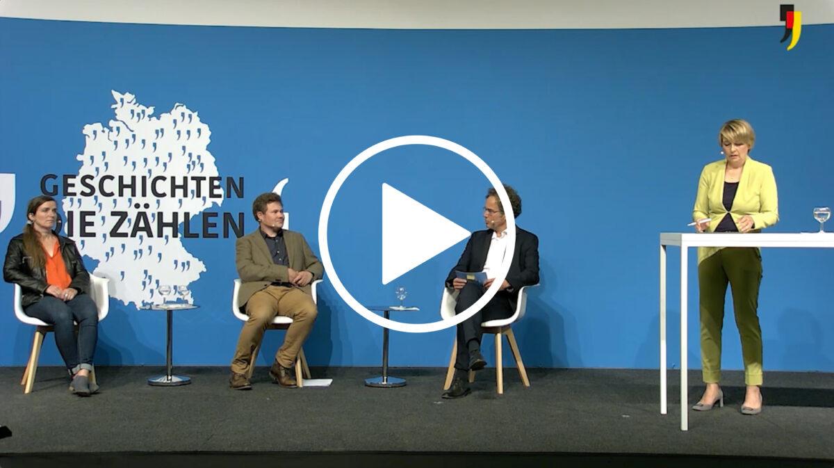 Drei Personen sitzen auf einer Bühne und sprechen miteinander. Eine Person steht an einem Stehtisch und hört zu.
