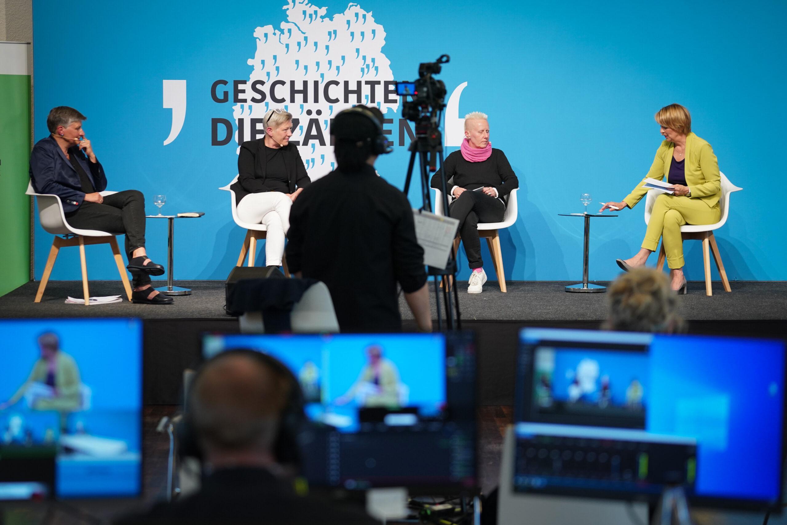 Vier Frauen sitzen auf einer Bühne und sprechen miteinander. Im Vordergrund befinden sich Kameras und Bildschirme.