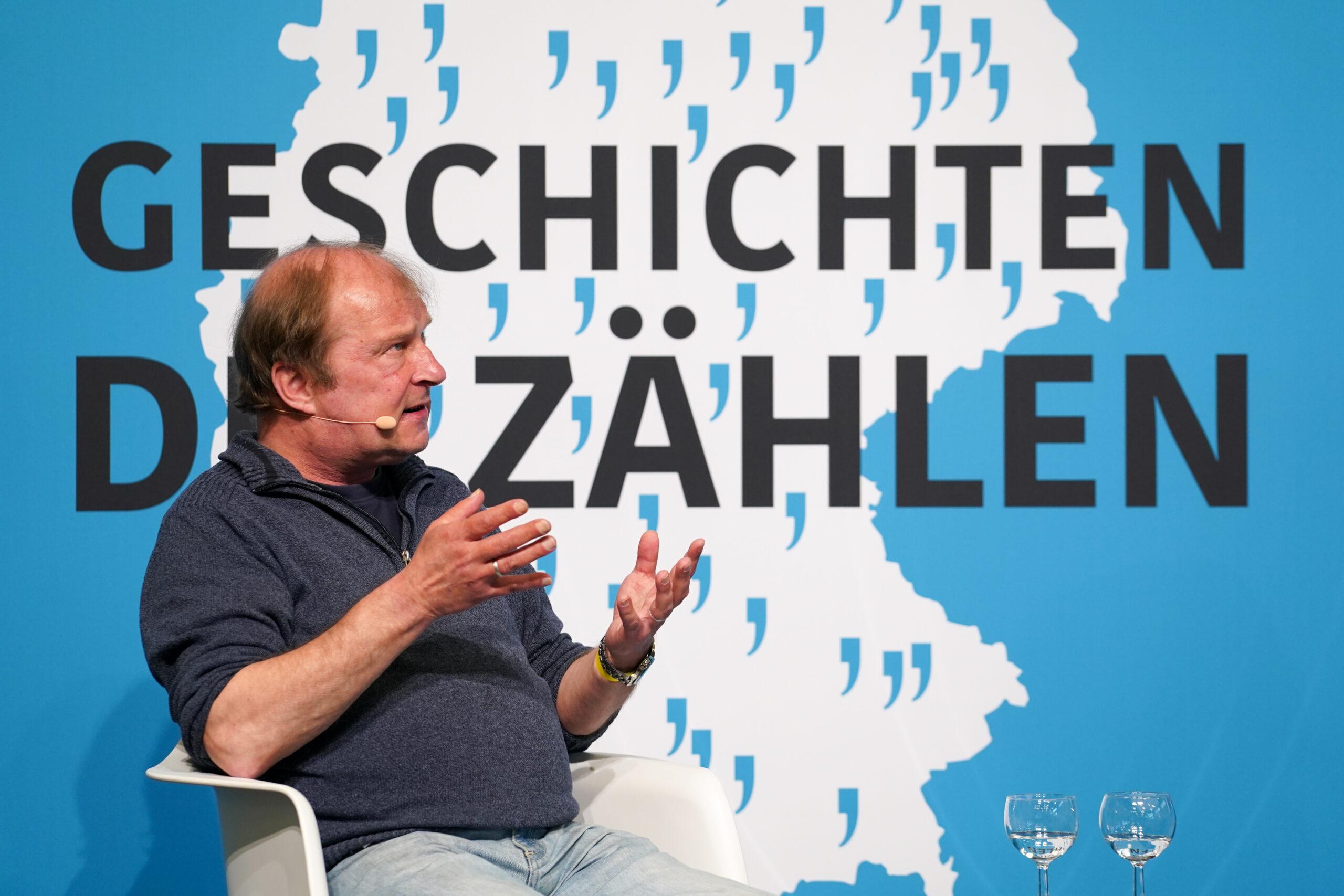 Ein Mann sitzt in einem Sessel und spricht. Hinter ist befindet sich das Bild einer Deutschlandkarte mit vielen Anführungszeichen und der Text: Geschichten, die zählen.
