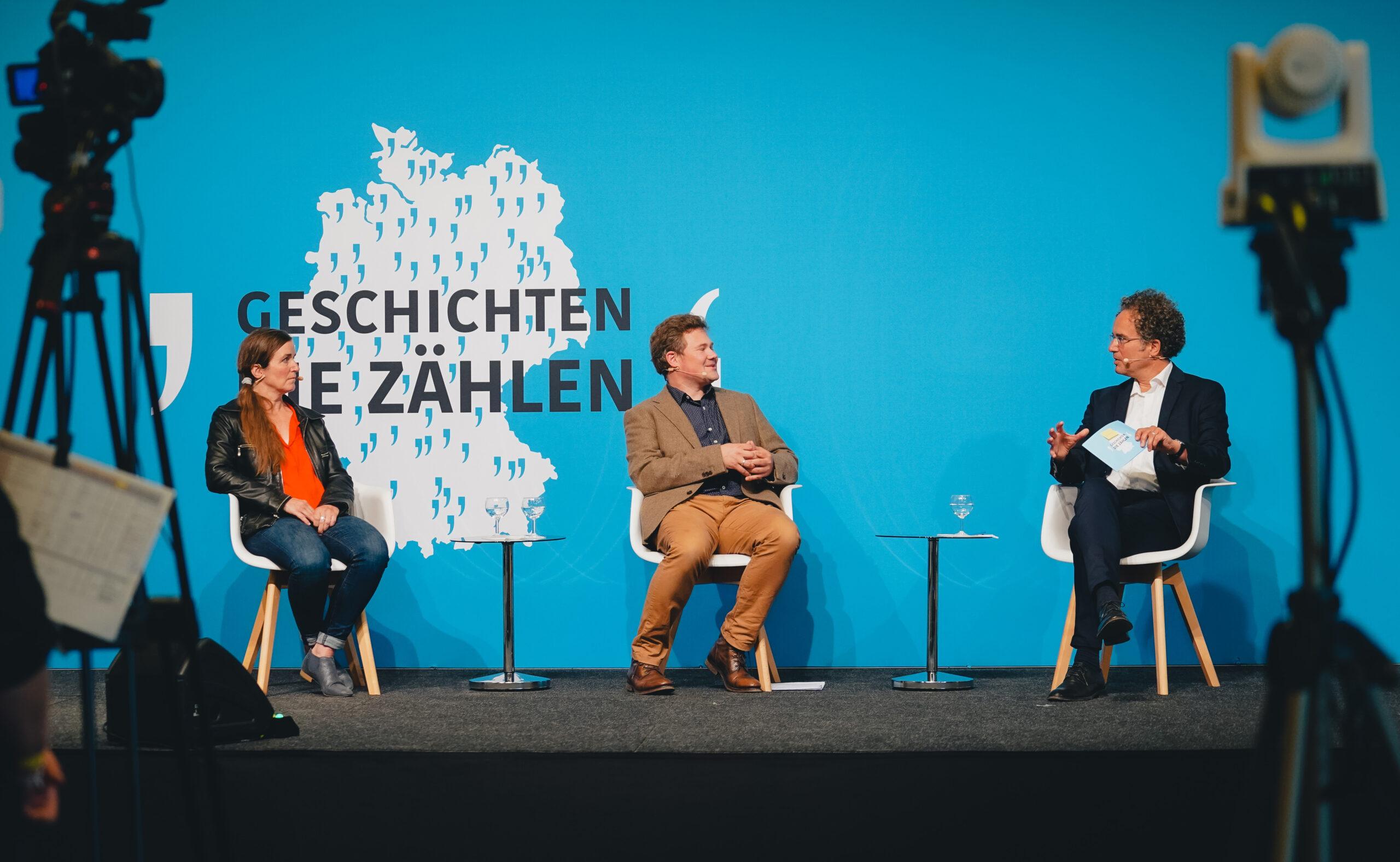 Eine Frau und zwei Männer sitzen auf einer Bühne und sprechen miteinander. Vor der Bühne befinden sich Kameras.