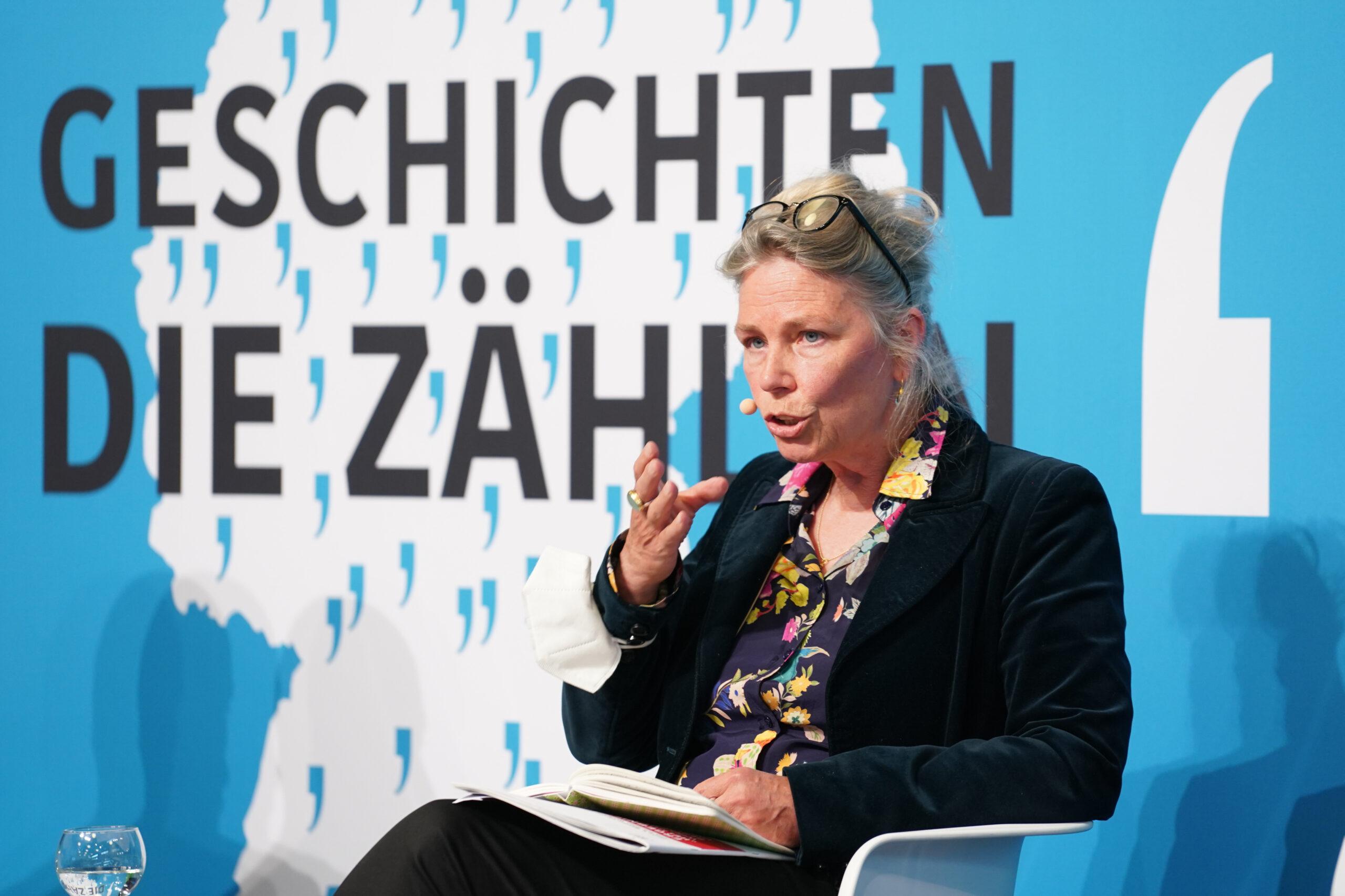 Eine Frau sitzt in einem Sessel und spricht. Hinter ist befindet sich das Bild einer Deutschlandkarte mit vielen Anführungszeichen und der Text: Geschichten, die zählen.