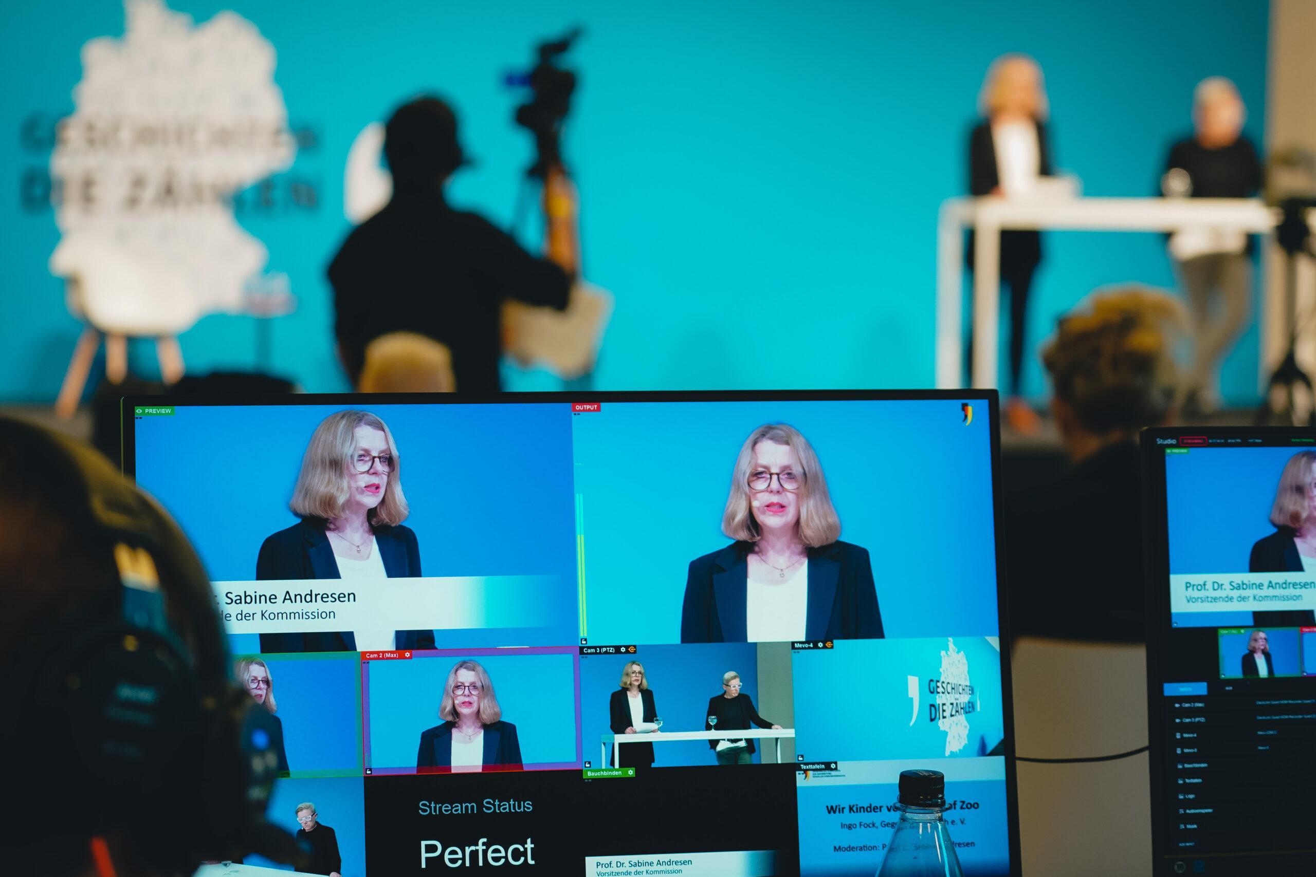Auf einem Bildschirm im Vordergrund befinden sich mehrere Personen, die in die Kamera schauen und sprechen. Im Hintergrund befinden sich eine Bühne und Kameras.